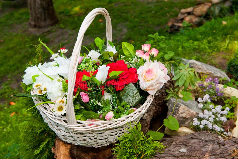 Vit vide- korg med ljusa konstgjorda blommor royaltyfri fotografi