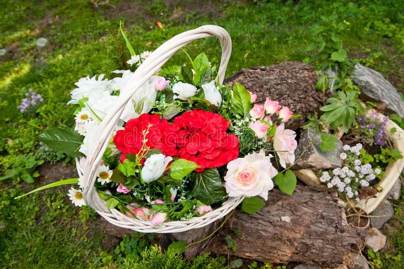 Vit vide- korg med ljusa konstgjorda blommor royaltyfri foto