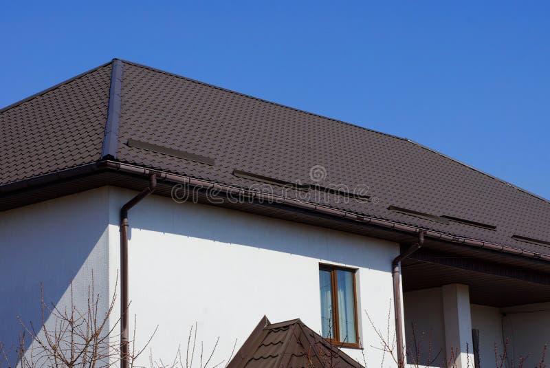 Vit vind som är hemmastadd med ett fönster och ett brunt belagt med tegel tak mot en blå himmel royaltyfri bild