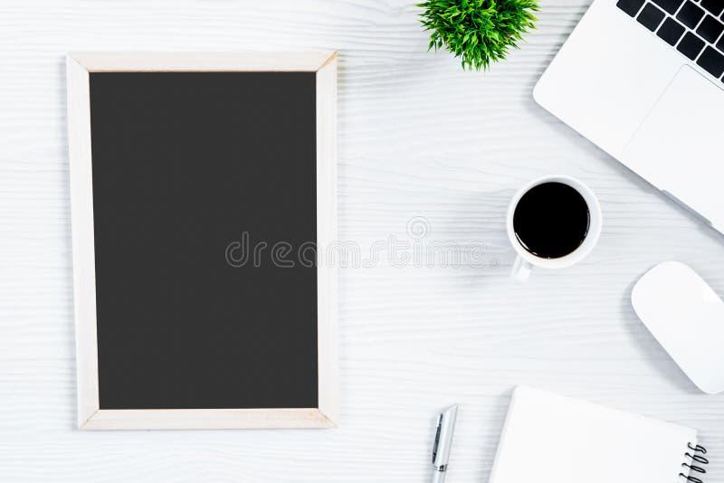 Vit wood tabell för kontorsskrivbord och utrustning för att arbeta med svart kaffe och tomt bräde i bästa sikt och plant strålbeg royaltyfri fotografi