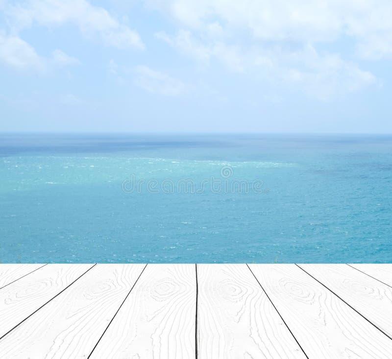 Vit wood tabell för tomt perspektiv över lodisar för suddighetshav och för blå himmel arkivbild