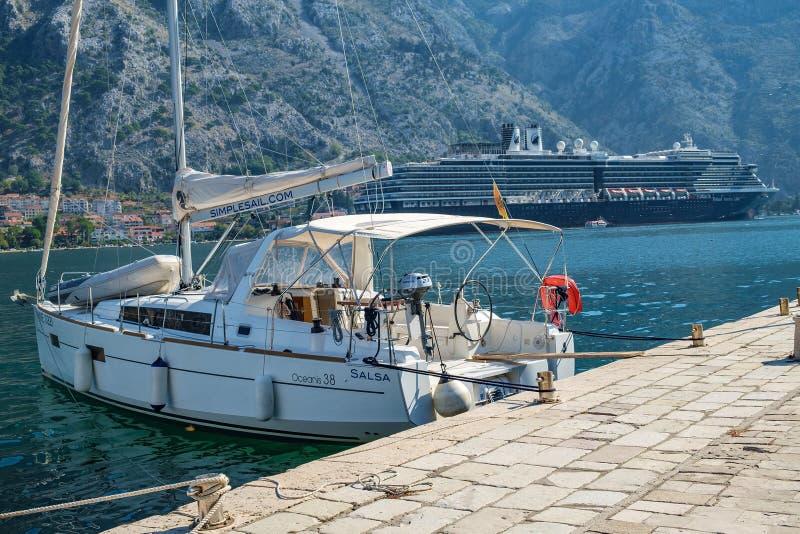 Vit yacht som förtöjas på pir på stranden Det enorma skeppet för passagerareeyeliner är kan ses i bakgrunden royaltyfri bild