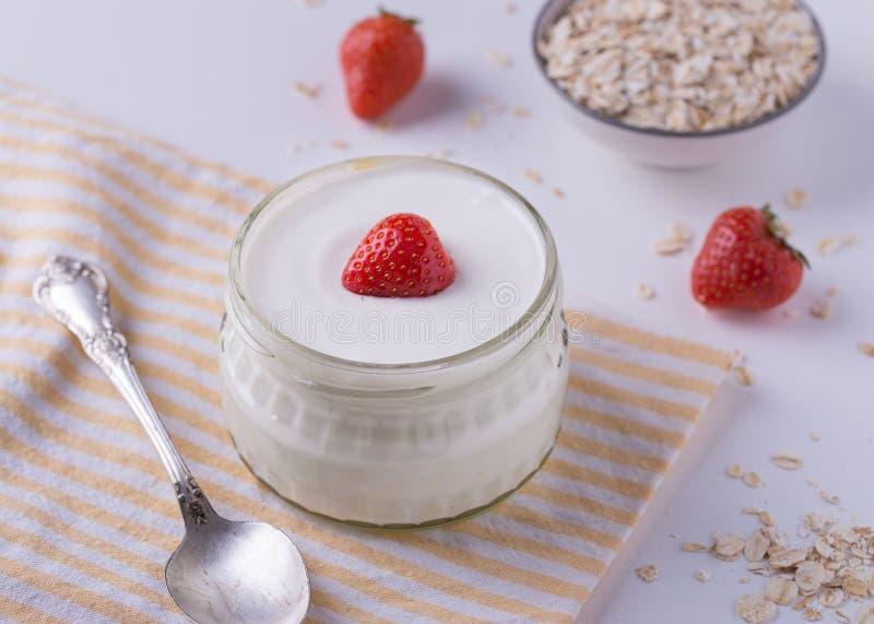 Vit yoghurt i den glass bunken med skeden och starwberries på vit bakgrund arkivfoto