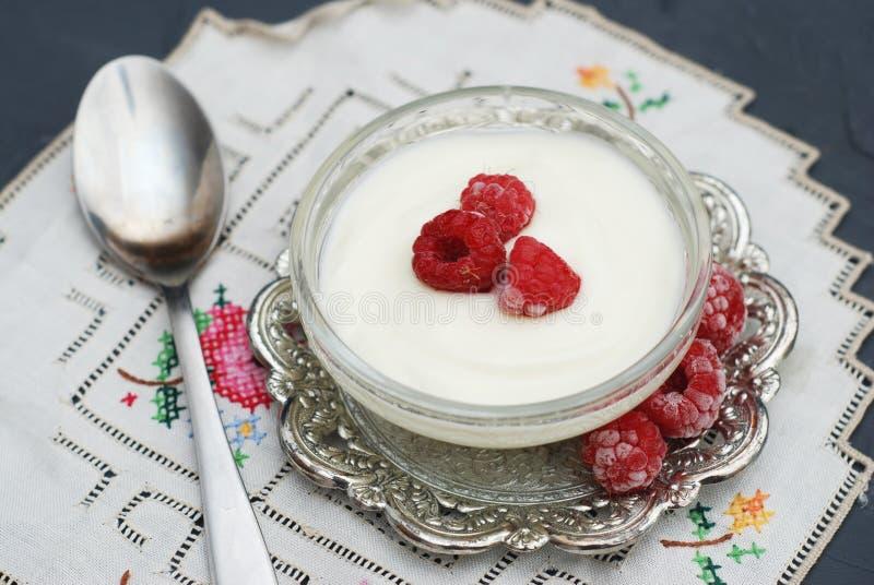 Vit yoghurt med hallon i den glass bunken på den lantliga tabellen med den broderade servetten Top beskådar royaltyfri fotografi
