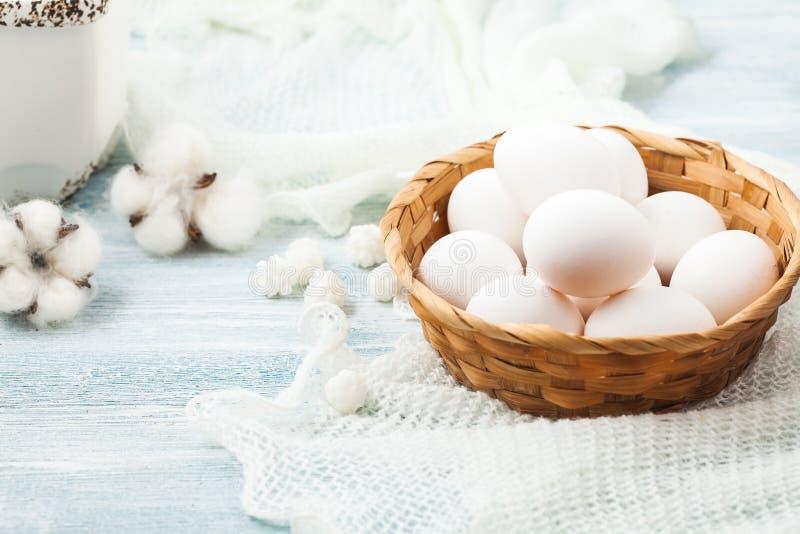 Vita ägg för påsk i en vide- korg på en ljus bakgrundsbakgrund för en vykort arkivfoto