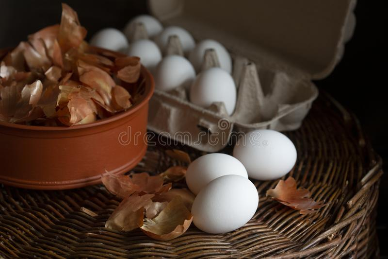 Vita ägg i en ask med en gul lök skalar i en maträtt på ett vide- magasin som förbereds för att färga i organisk färg fö arkivfoton