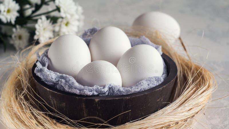 Vita ägg i träbunke på vit bakgrund, selektiv focuse arkivfoto