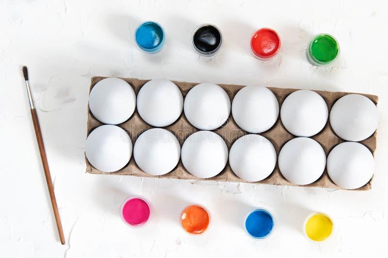 Vita ägg och målarfärger på en vit bakgrund Färgläggningpåskägg royaltyfri fotografi