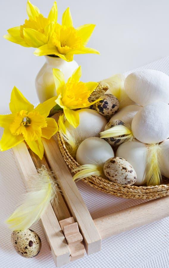 vita ägg, vaktelägget och fjädern i korgen med påskliljor blommar arkivfoto