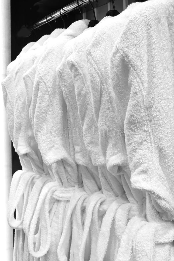 Vita badrockar, kuddar, handdukar som hänger i trägarderob av tjänste- rum i hotell royaltyfri fotografi