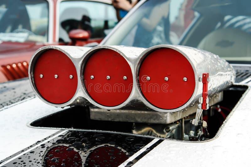 Vita band p? huven och turboladdarekompressorn med r?da drosels p? amerikan muskelbilen fotografering för bildbyråer