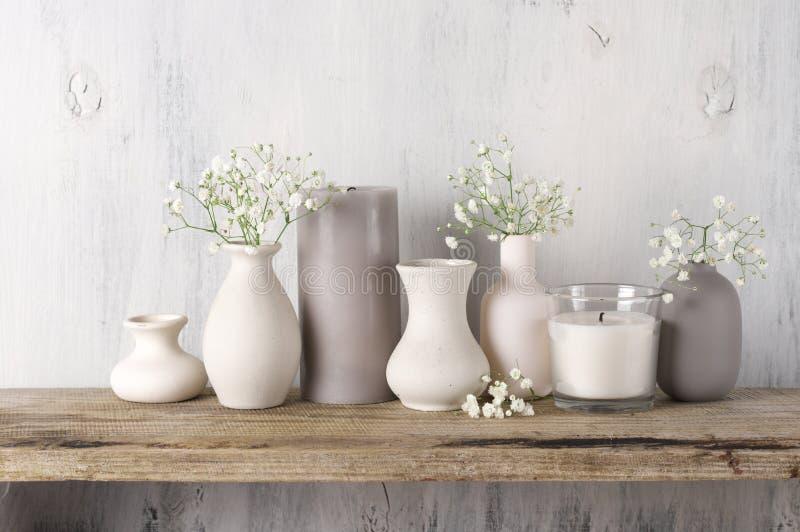 Vita blommor i neutralt färgade vaser och stearinljus royaltyfri foto
