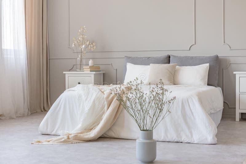 Vita blommor i vas i det eleganta gråa sovrummet som är inre med enkel sängkläder royaltyfri foto