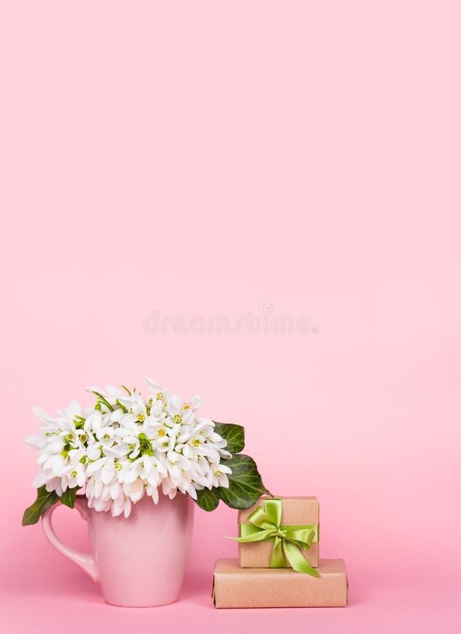 Vita blommor och gåvaask Galanthus på rosa bakgrund snowdrops arkivfoton