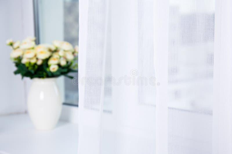 Vita bomullsgardin och blommor på fönstret royaltyfri fotografi