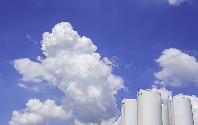 Vita bränslebehållare och skönheten av himlen med moln och solen i sommar royaltyfri fotografi