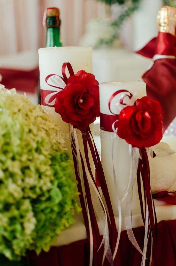 Vita bröllopstearinljus dekorerade med röda rosor och band royaltyfri fotografi
