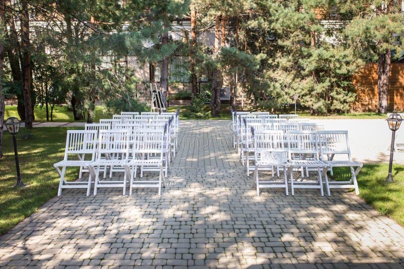 Vita bröllopstolar med buketter av lavendel utomhus Det är mycket vita stolar på en grön gräsmatta royaltyfri foto