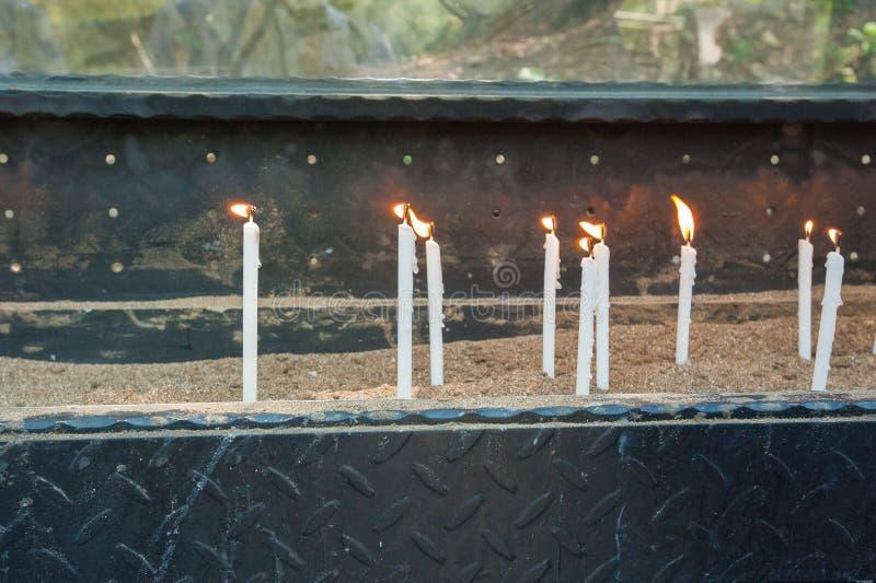Vita brinnande stearinljus står på sanden royaltyfria bilder