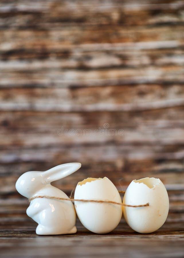 Vita Bunny Porcelain Pulling Broken Egg skal royaltyfri foto