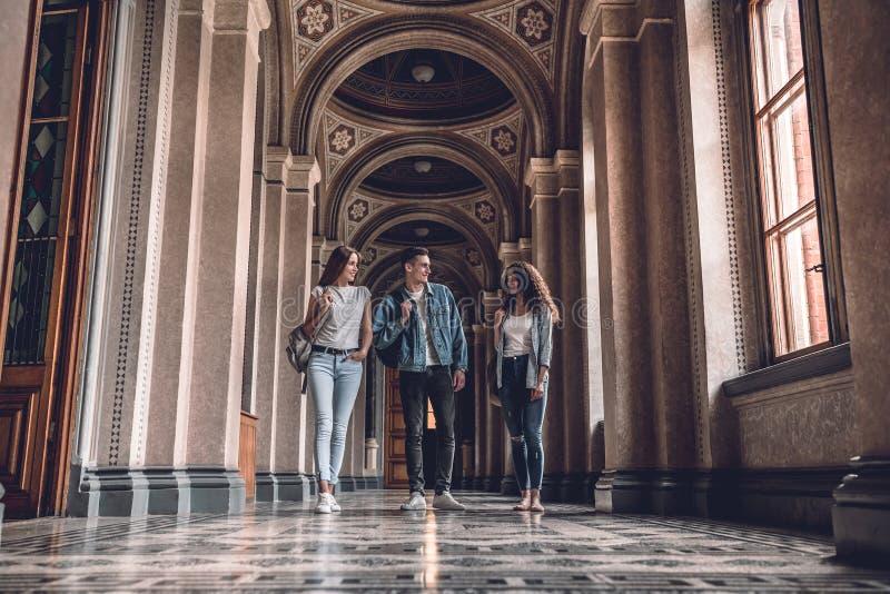 Vita dell'istituto universitario Giovani studenti che camminano nell'università e parlare a vicenda fotografie stock