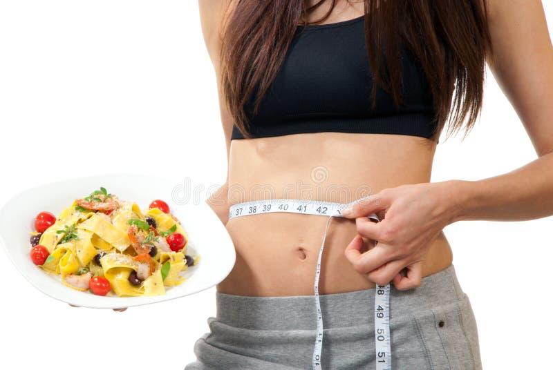 Vita di misurazione della donna e tenere l'alimento di dieta immagini stock