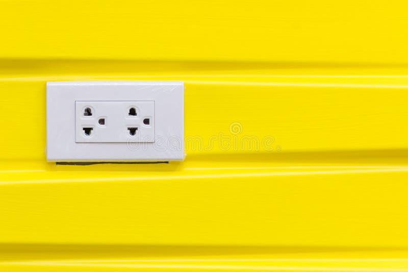 Vita elektriska proppar på den moderna gula tapeten arkivfoto