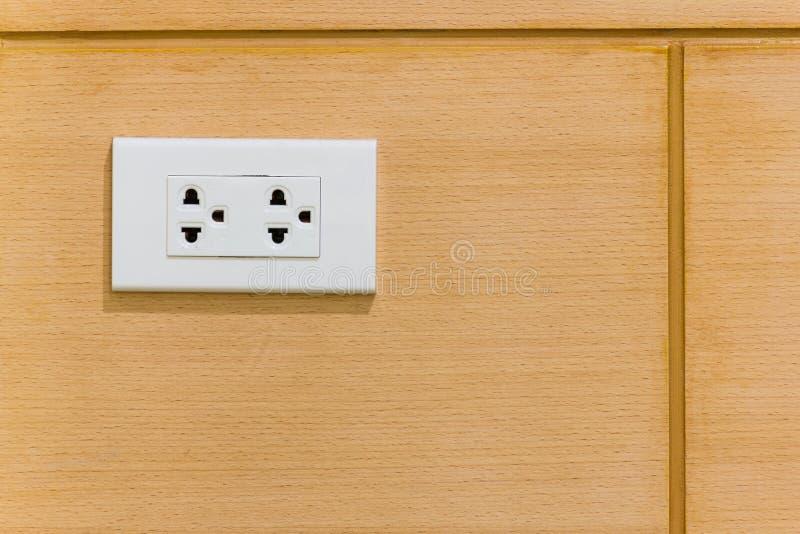 Vita elektriska proppar på tappning bryner den wood väggen fotografering för bildbyråer