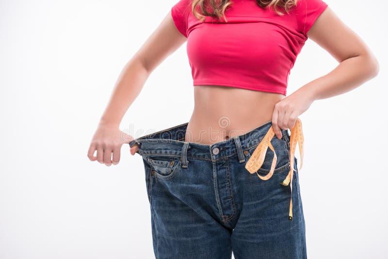 Vita esile della giovane donna in grandi jeans con fotografia stock