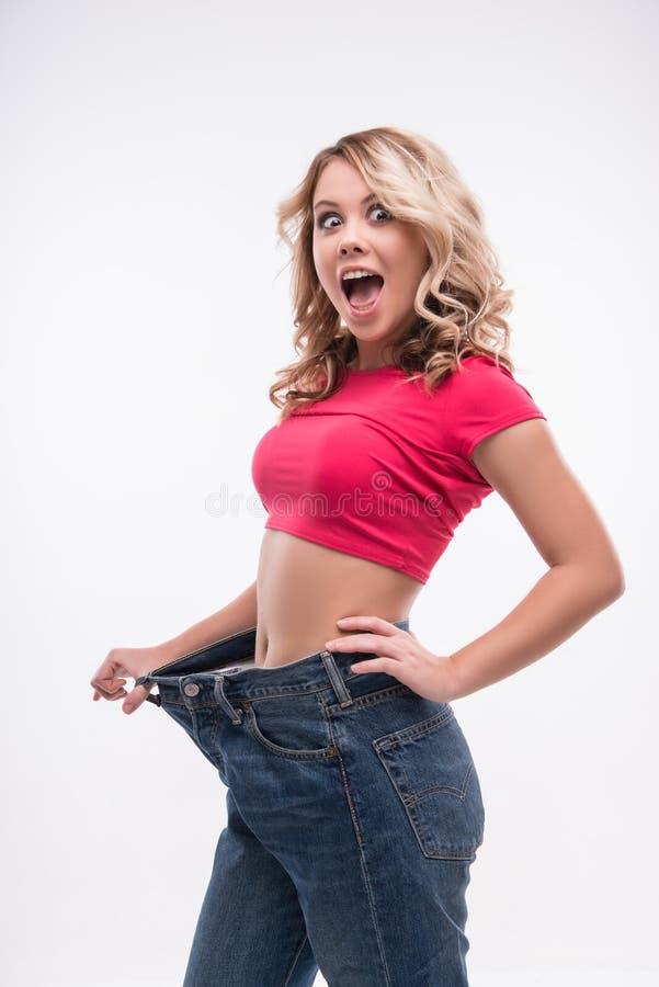 Vita esile della giovane donna nella grande mostra dei jeans fotografie stock