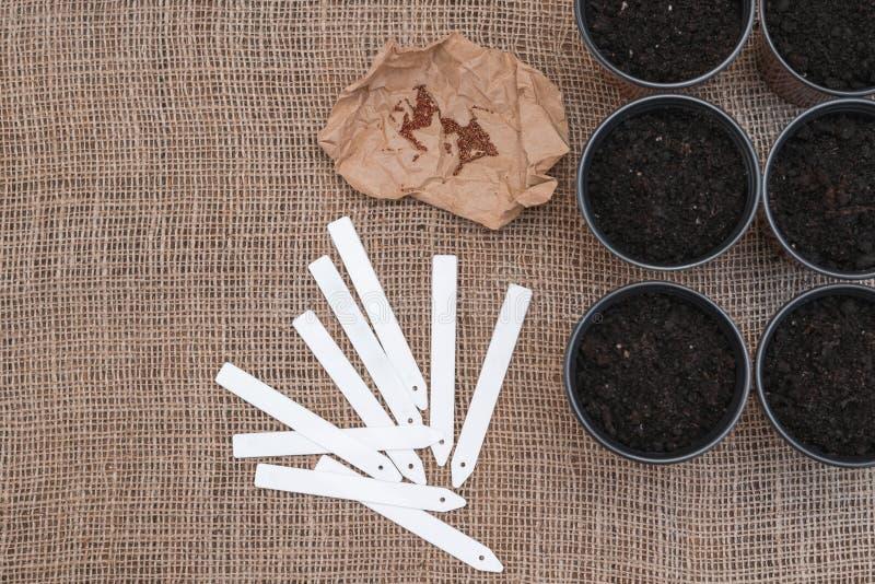 Vita etiketter och bruna krukor med jord på säckvävbakgrund arkivfoto