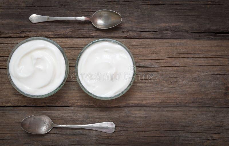 Vita exponeringsglasbunkar för yoghurt itu på det gamla träskrivbordet med två skedar bredvid royaltyfria foton