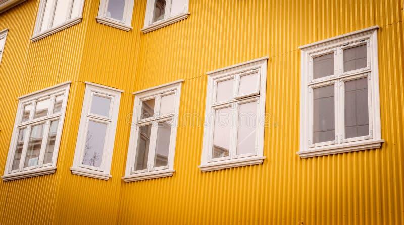 Vita fönster på en gul fasad royaltyfria bilder