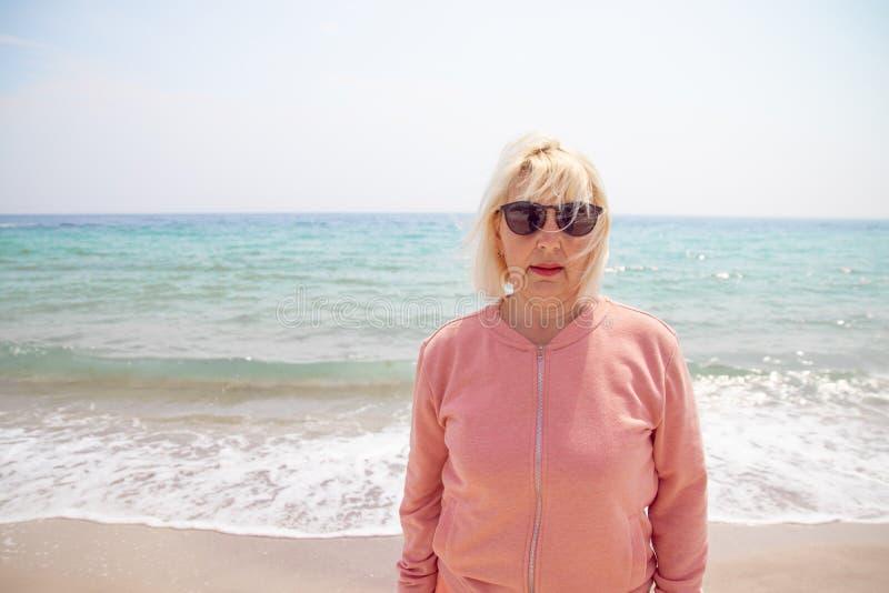 Vita felice Donna bionda adulta che cammina sulla spiaggia dell'oceano un giorno soleggiato Vita felice fotografia stock