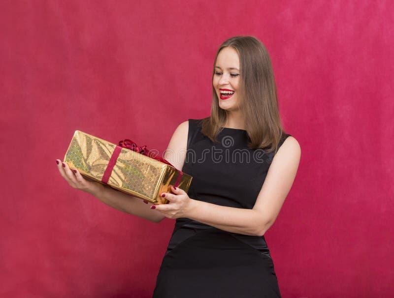 1 vita flicka i svart klänning med gåvaasken på röd bakgrund, gir fotografering för bildbyråer