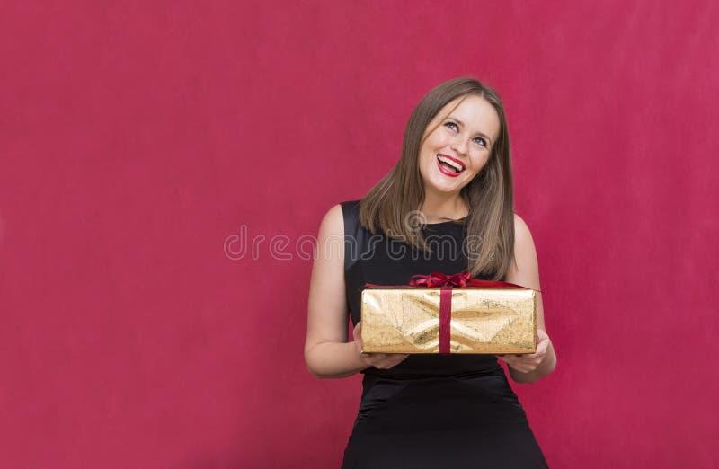 1 vita flicka med en gåva i hennes händer jublar att skratta på ett rött arkivbild