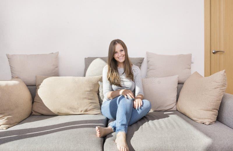 1 vita flicka med långt hår i jeans som sitter på soffan, barn royaltyfri foto