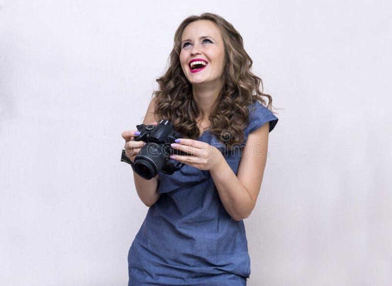 1 vita flicka med lockigt hår och en blå klänning med en kamera i hennes händer, en ung kvinna skrattar, jublar royaltyfri fotografi