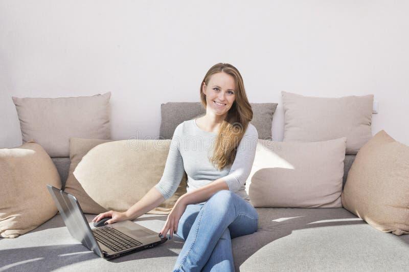 1 vita flicka på soffan med en bärbar dator, sammanträde för ung kvinna på royaltyfria bilder