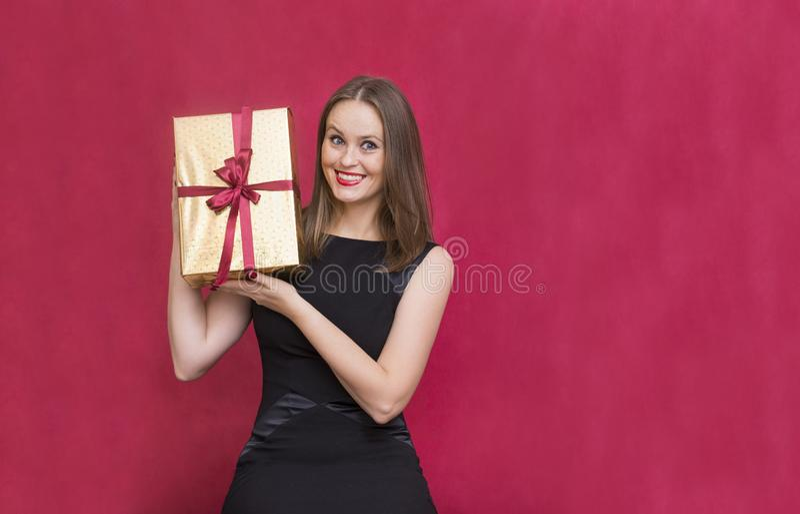 1 vita flicka som rymmer en guld- ask i en gåvaask på en röd backgro royaltyfria bilder