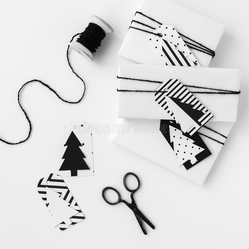 Vita gåvor med prydliga gåvaetiketter, tappningsax och tråden rullar royaltyfri bild