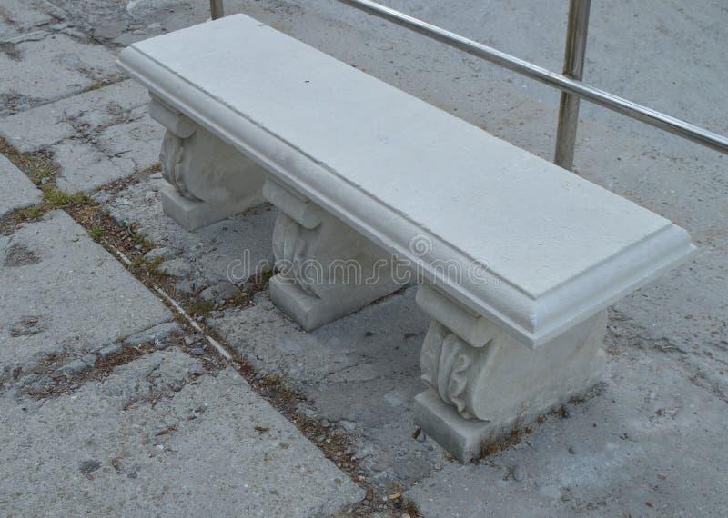 Vita gamla ställningar för konkret bänk på stranden arkivbilder