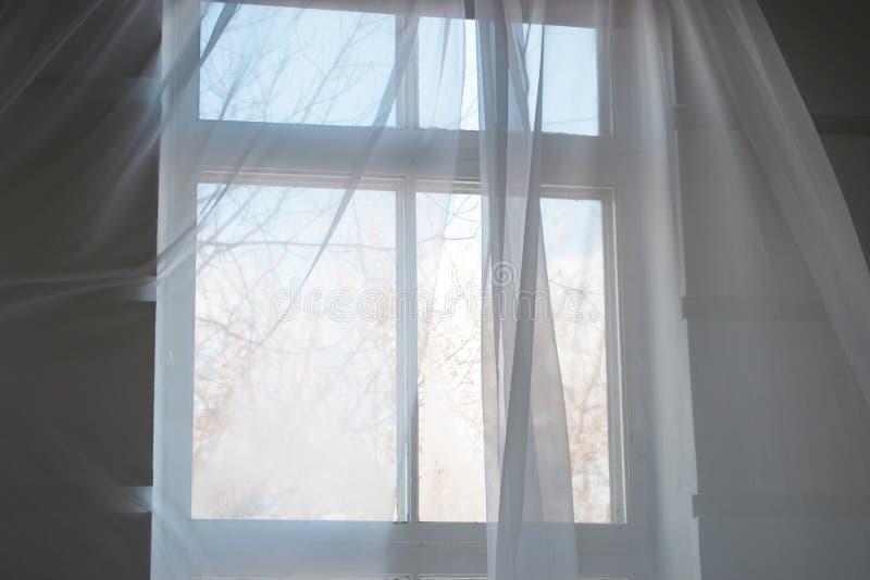 Vita genomskinliga gardiner på fönstret med blå himmel för vår royaltyfria bilder