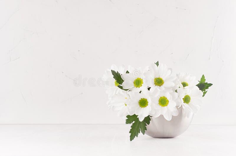 Vita gerberas för härlig ny vår med gula ögon i modern vas för silver i modern mjuk ljus vit inre royaltyfria bilder