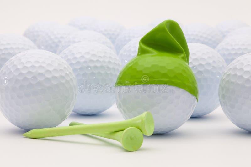 Vita golfbollar med det roliga locket på den vita bakgrunden royaltyfria bilder