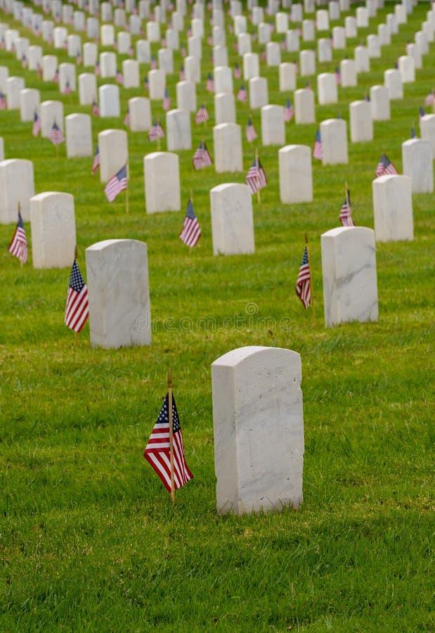 Vita gravstenar på den nationella kyrkogården med små flaggor royaltyfria bilder
