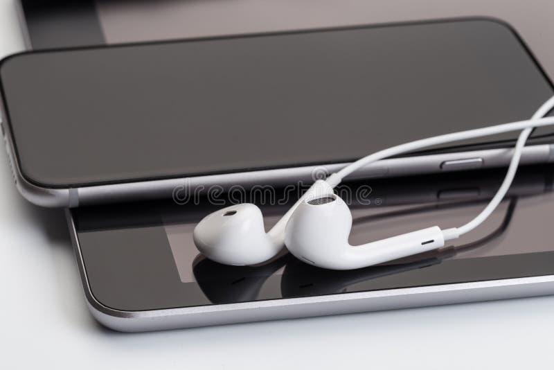 Vita hörlurar på minnestavlan och telefonen arkivfoto