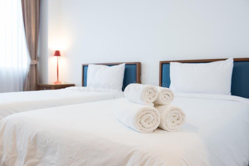 Vita handdukar på säng i hotellrum royaltyfri foto