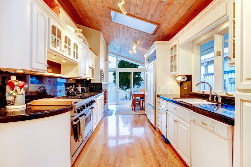 Vita köksskåp med svart räknareblast i lyxigt hus royaltyfria bilder