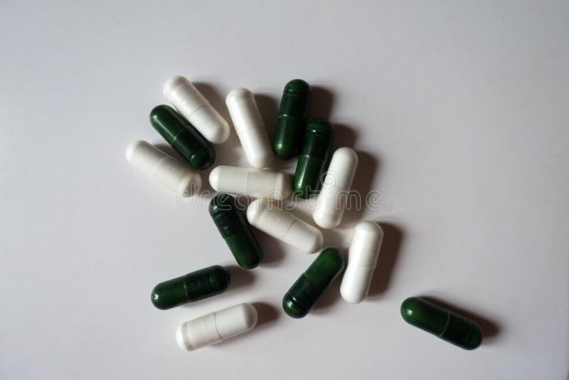 Vita kapslar av magnesiumcitrate och gröna kapslar av multivatamins från över arkivbilder